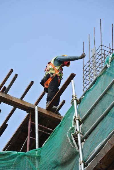 Ouvrier du bâtiment se dresse sur des planches branlantes sur un chantier de construction en altitude et baisse les yeux