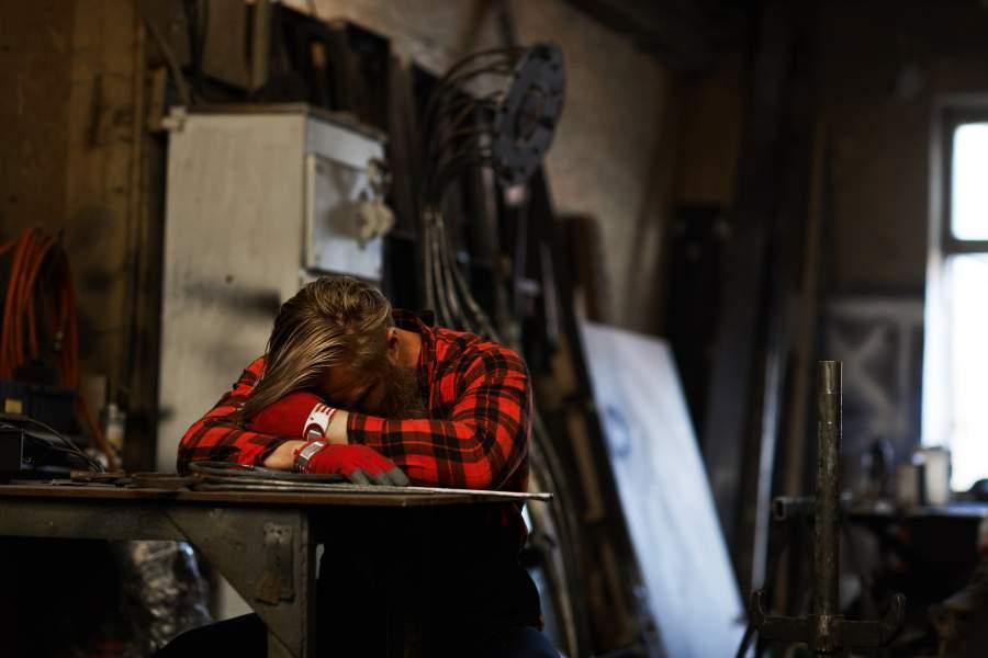 le travailleur fatigué qui dort la tête sur les bras à une table en milieu de travail a besoin de repos pour réduire la fatigue