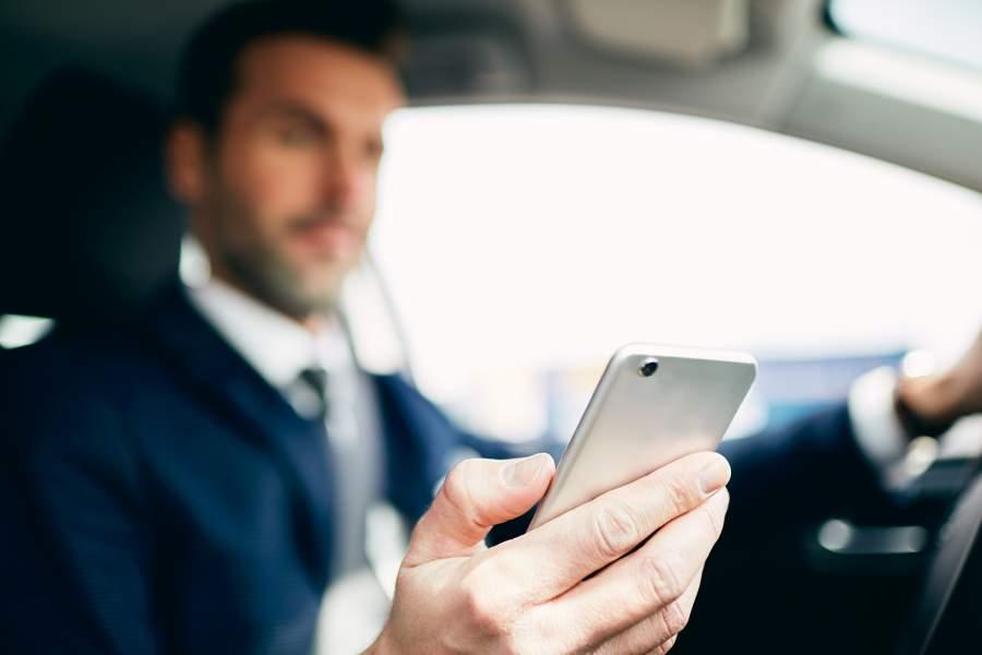 L'homme en costume s'assoit au volant d'une voiture et regarde son smartphone dans sa main et se laisse distraire délibérément.