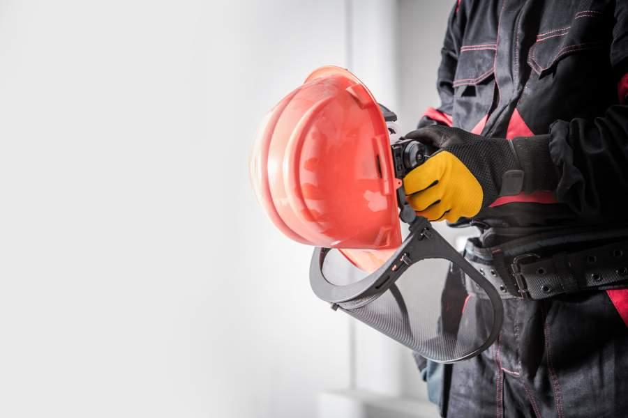 Un employé vêtu de vêtements de travail et de gants de sécurité tient un casque de sécurité orange avec un pare-soleil dans les mains.