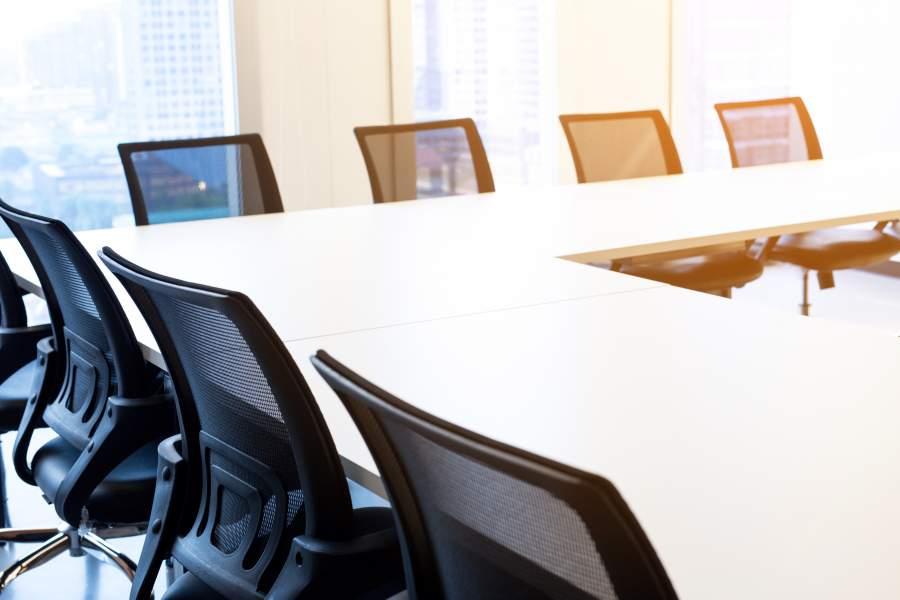 Quelques chaises vides confortables avec des dossiers noirs aux tables blanches au-dessus du coin en formation d'atelier pour des rondes de discussion ouvertes.