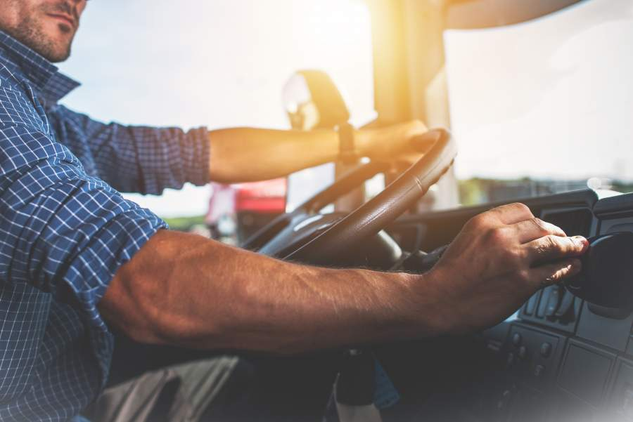 Un homme en chemise à carreaux conduit une voiture et regarde le tableau de bord au lieu de se concentrer sur la route.